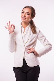 Heureux souriant belle jeune femme d'affaires montrant un geste correct, sur un mur gris. modèle blond caucasien dans le concept de présentation d'entreprise. composition carrée.