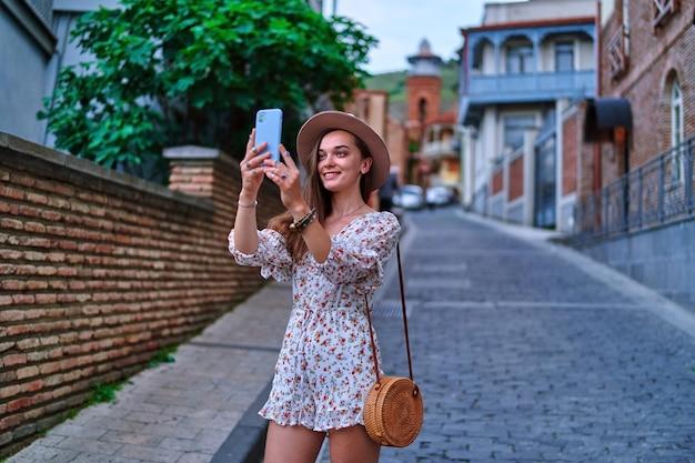 Heureux souriant belle jolie jeune fille joyeuse voyageur prenant une photo sur un appareil photo de téléphone pendant le week-end de vacances tout en visitant