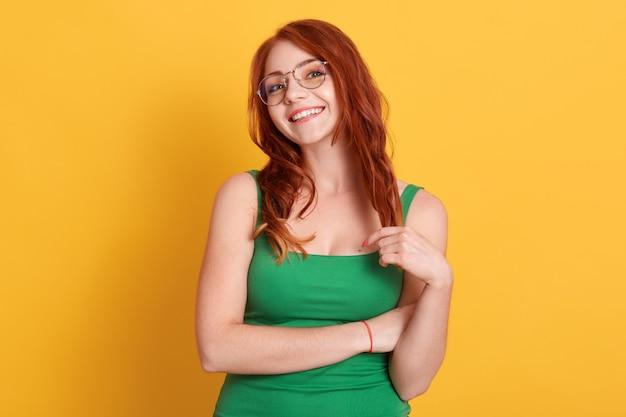 Heureux souriant cheveux roux belles robes féminines t-shirt sans manches vert, regardant la caméra avec un sourire charmant