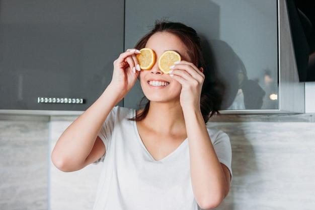 Heureux souriant drôle belle fille jeune femme ferme les yeux de citron dans la cuisine