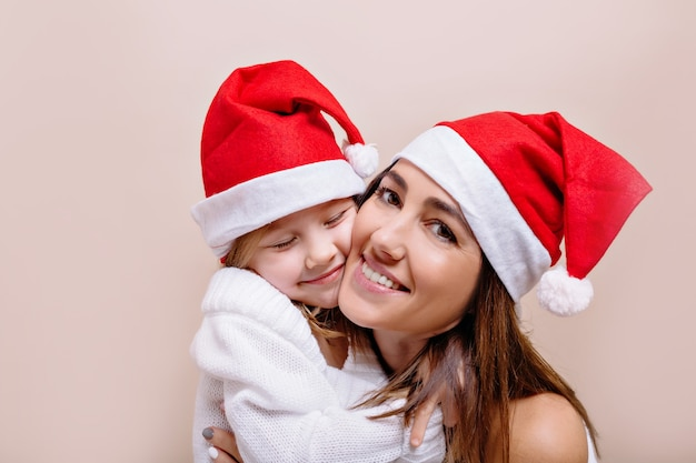 Heureux, souriant drôle mère et fille posent et tiennent leurs visages portant des casquettes du père noël. une belle jeune femme aux lèvres brillantes tient une fille de 5 ans.