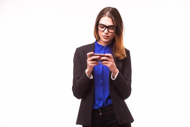 Heureux souriant femme d'affaires prospère avec téléphone portable, isolé sur un mur blanc