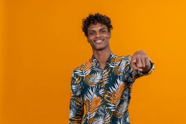Heureux et souriant jeune bel homme à la peau foncée aux cheveux bouclés en chemise imprimée de feuilles tout en pointant avec le doigt