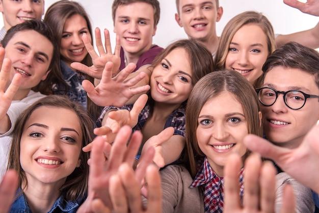 Heureux souriant jeune groupe d'amis sur gris
