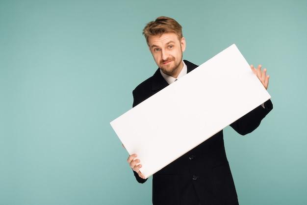Heureux souriant jeune homme d'affaires montrant une pancarte vierge, sur bleu