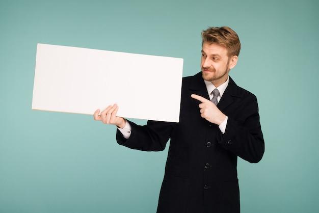 Heureux souriant jeune homme d'affaires pointe le panneau vierge du doigt, sur le bleu