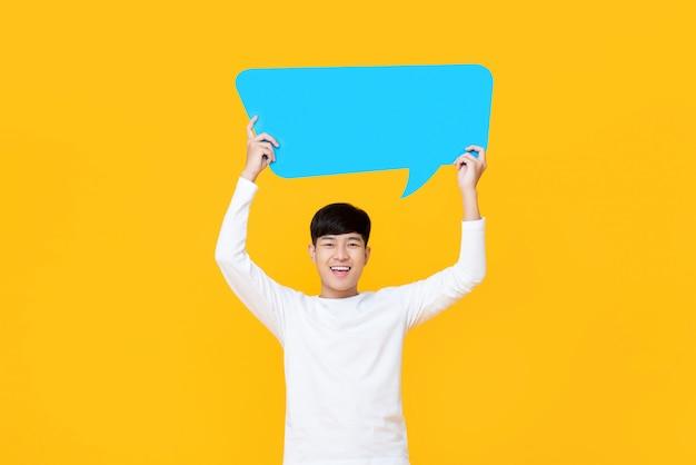 Heureux souriant jeune homme asiatique mignon tenant la bulle de dialogue bleu