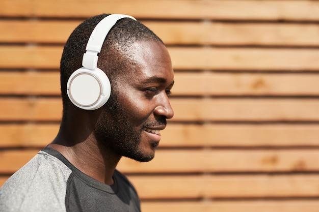 Heureux sportif africain profitant de la musique dans des écouteurs sans fil tout en s'entraînant à l'extérieur