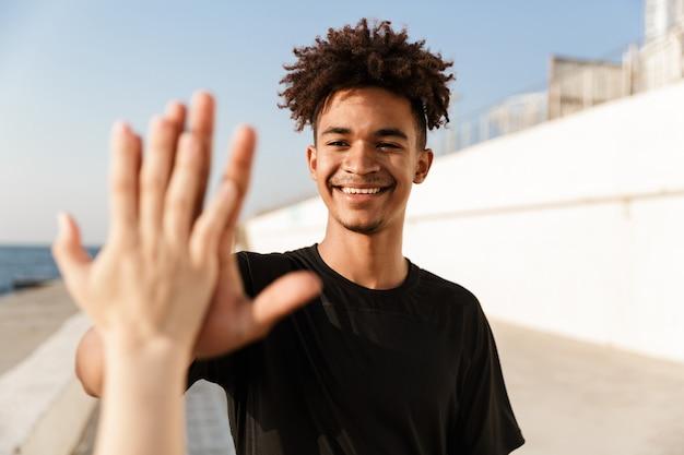 Heureux sportif en plein air sur la plage donne un cinq à la main de quelqu'un