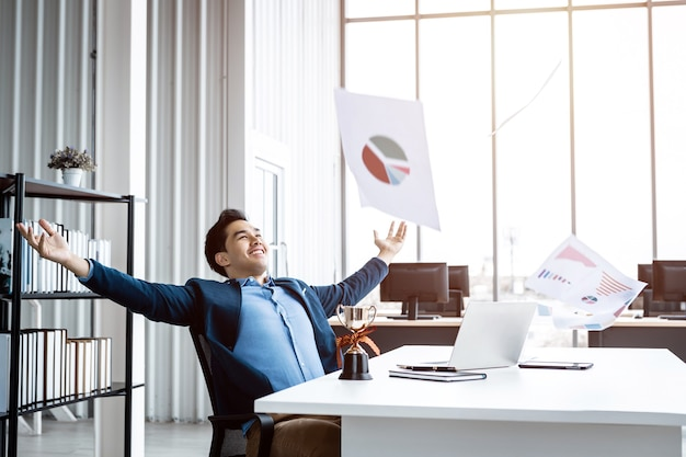 Heureux succès d'un jeune homme d'affaires asiatique pour avoir lancé le plan d'affaires dans un document papier en l'air, un ordinateur portable et une coupe de champion sur fond de table au bureau, émotionnellement satisfait de