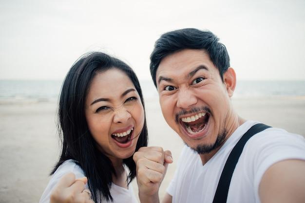 Heureux et succès ouais visage du couple touristique en voyage de vacances à la plage romantique.