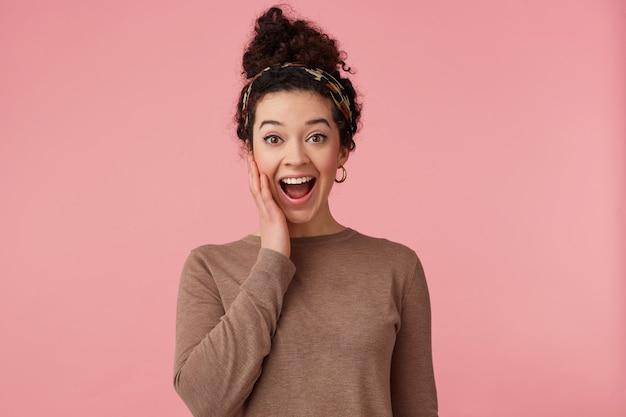 Heureux surpris jeune belle femme aux cheveux noirs bouclés, a entendu les nouvelles fraîches, largement souriant, touchant la joue et regardant la caméra avec des yeux grands ouverts isolés sur fond rose.