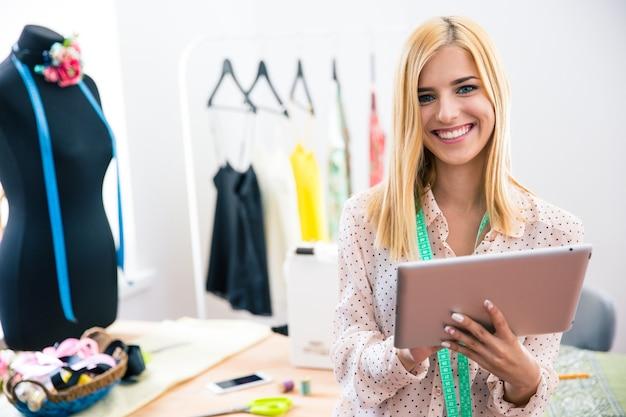Heureux tailleur féminin tenant ordinateur tablette