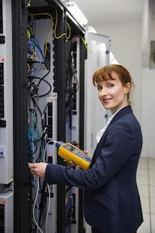 Heureux technicien utilisant un analyseur de câble numérique sur serveur