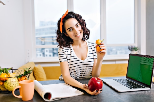 Heureux temps de détente à la maison de joyeuse jeune femme aux cheveux bouclés coupés souriant sur la table dans le salon. ordinateur portable avec écran vert, agrumes, pomme, magazine, thé, refroidissement dans un appartement moderne