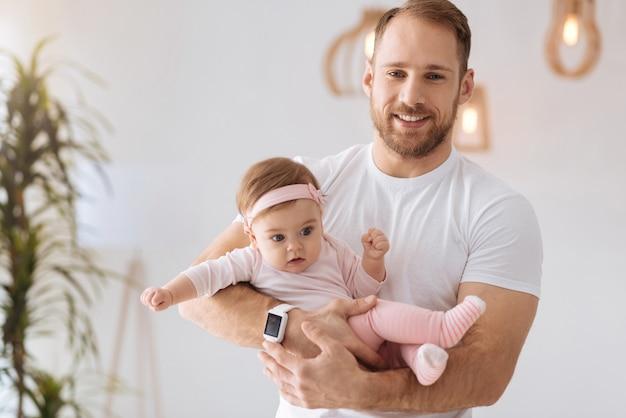 Heureux temps de père. athlétique fort heureux père debout à la maison et tenant le nouveau-né dans ses bras tout en exprimant des émotions positives