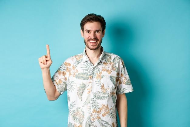 Heureux touriste en chemise hawaïenne souriant et pointant le doigt vers le haut, montrant la promotion du logo, debout sur fond bleu.