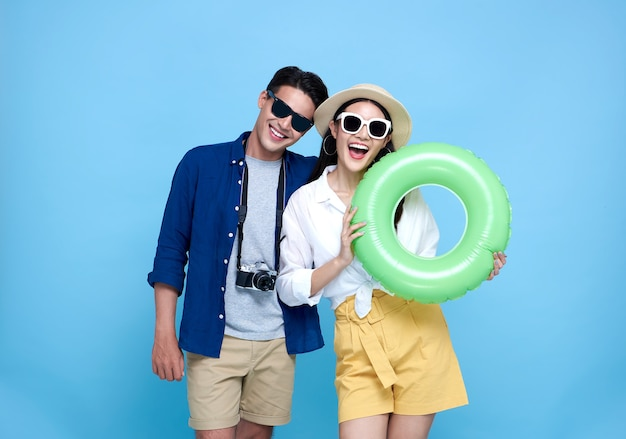 Heureux touriste de couple asiatique ludique vêtu de vêtements d'été et d'accessoires de plage pour voyager en vacances sur le bleu.