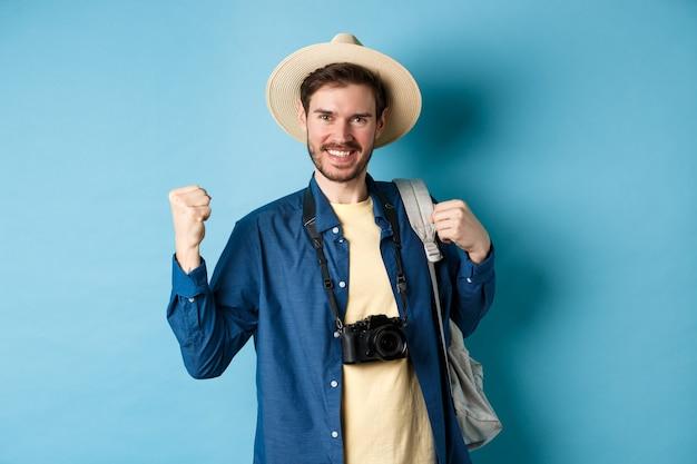 Heureux touriste profitant des vacances d'été, souriant et disant oui avec une pompe à poing, célébrant les vacances, ressentant de la joie en finissant par voyager à l'étranger, debout sur fond bleu.
