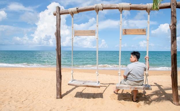 Heureux touriste s'asseoir et se détendre sur la balançoire en bois devant la plage, se détendre et se reposer sur le concept de vacances