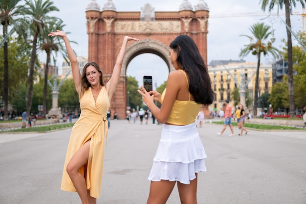 Heureux touristes féminins prenant des photos sur la place de la ville