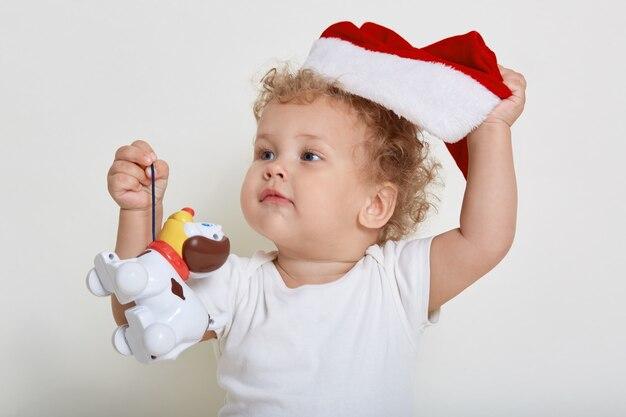 Heureux tout-petit garçon en bonnet de noel jouant avec des jouets, regardant ailleurs et mettant de sa casquette