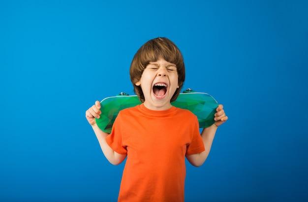 Heureux tout-petit garçon en t-shirt orange détient skateboard sur une surface bleue avec un espace pour le texte