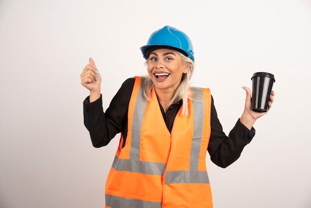 Heureux travailleur de la construction ayant une pause avec une tasse de thé. photo de haute qualité