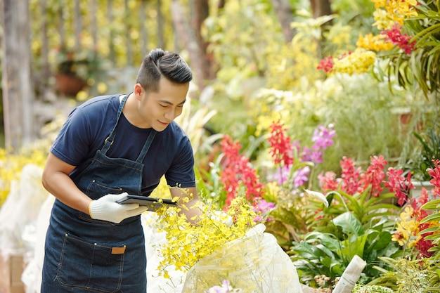 Heureux travailleur de pépinière de fleurs mâles avec tablette numérique déballant des plantes recouvertes de matériau non tissé