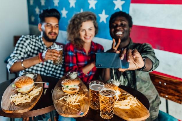 Heureux trois amis dans un restaurant de restauration rapide prenant un selfie pendant qu'ils mangent des hamburgers et boivent de la bière