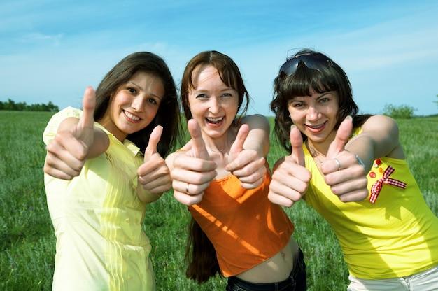 Heureux trois amis show sign ok dans le champ vert sous ciel bleu