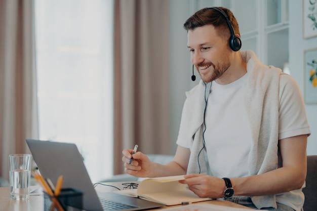 Heureux tuteur masculin donne des cours en ligne communique à distance avec le stagiaire utilise des écouteurs avec microphone et ordinateur portable prend les notes nécessaires dans les poses de journal dans l'espace de coworking. processus d'apprentissage en ligne