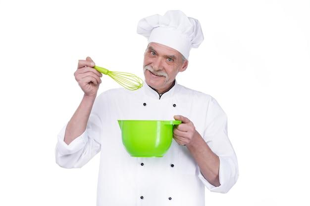 Heureux vieux chef cuisinier tenant un bol et fouettant quelque chose avec un fouet