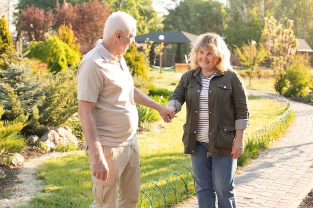 Heureux vieux couple caucasien âgé souriant dans le parc par une journée ensoleillée, couple de personnes âgées se détendre au printemps été. mode de vie de soins de santé personnes âgées retraite couple amoureux ensemble concept de la saint-valentin