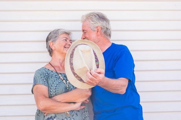 Heureux vieux couple souriant avec un chapeau à la main par une journée ensoleillée avec un mur en bois blanc - des personnes âgées joyeuses apprécient le style de vie avec amour et plaisir ensemble