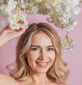 Heureux visage de femme tenant un bouquet de fleurs blanches