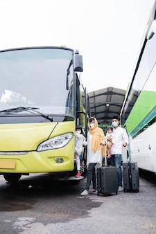 Heureux voyage de vacances musulmanes asiatiques dans un bus avec famille portant un masque empêchant la propagation du virus