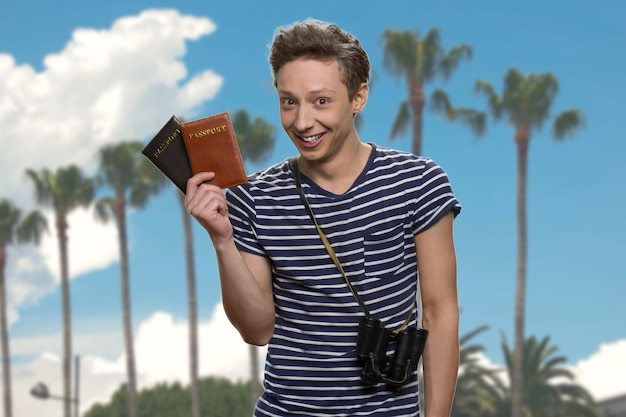 Heureux voyageur adolescent excité tenant des passeports. arbres tropicaux et ciel bleu en arrière-plan.
