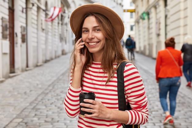 Heureux voyageur appelle l'opérateur via téléphone portable, écoute les avantages internet, se dresse en plein air sur fond de rue floue