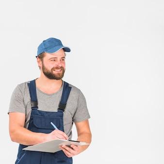 Heureux wan en casquette et écriture générale sur le presse-papiers