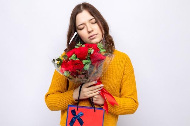 Heureux avec les yeux fermés belle jeune fille tenant un sac cadeau avec bouquet