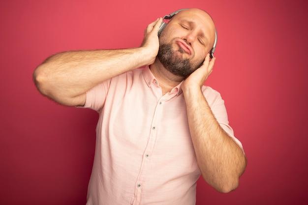 Heureux avec les yeux fermés homme chauve d'âge moyen portant un t-shirt rose et un casque isolé sur rose