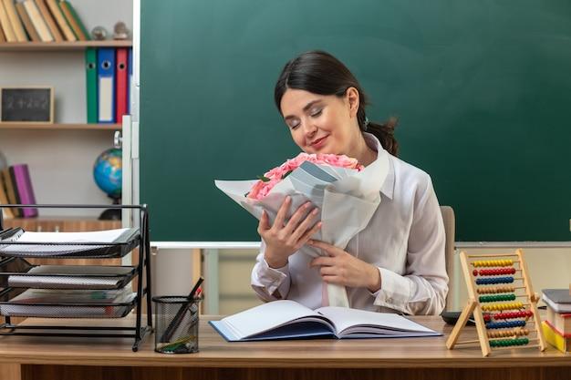 Heureux avec les yeux fermés jeune enseignante tenant un bouquet assis à table avec des outils scolaires en classe