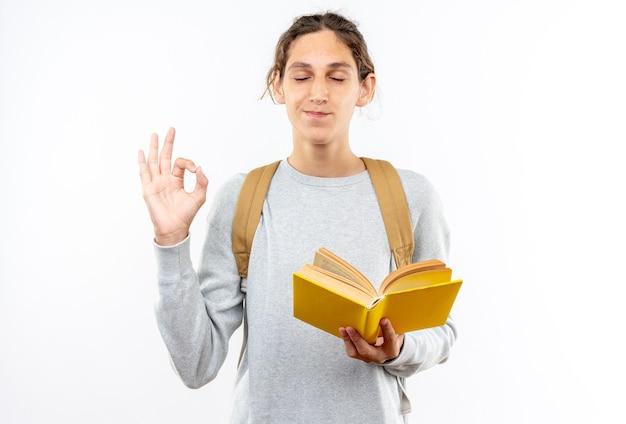 Heureux avec les yeux fermés jeune étudiant portant un sac à dos tenant un livre faisant de la méditation isolé sur un mur blanc