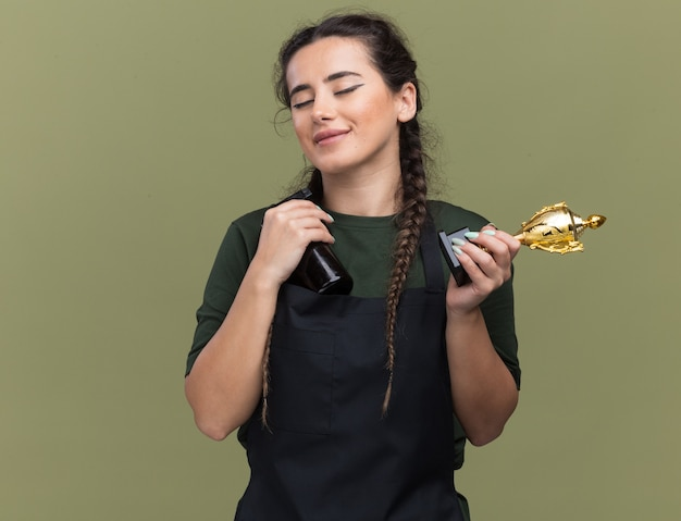Heureux les yeux fermés jeune femme coiffeur en uniforme tenant la coupe du gagnant avec une tondeuse à cheveux isolé sur mur vert olive