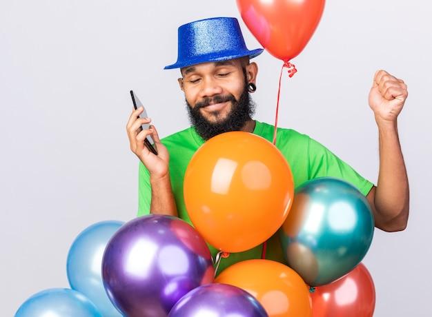 Heureux avec les yeux fermés, jeune homme afro-américain portant un chapeau de fête debout derrière des ballons, tenant un téléphone et montrant un geste oui isolé sur un mur blanc