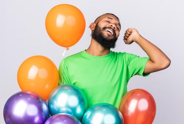 Heureux avec les yeux fermés, jeune homme afro-américain portant un chapeau de fête debout parmi des ballons montrant un geste oui isolé sur un mur blanc
