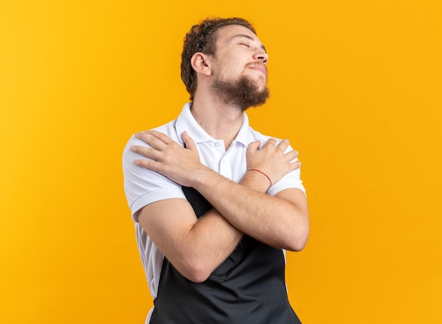 Heureux avec les yeux fermés jeune homme barbier en uniforme mettant les mains sur l'épaule isolé sur mur jaune