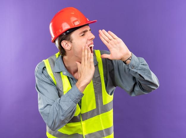 Heureux avec les yeux fermés jeune homme de construction en uniforme appelant quelqu'un
