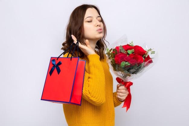 Heureux avec les yeux fermés montrant le geste de baiser belle jeune fille tenant un sac-cadeau avec bouquet